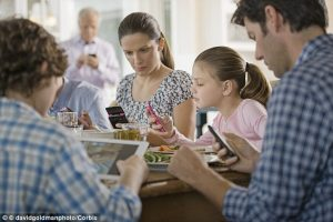 Family eating dinner looking at cell phones